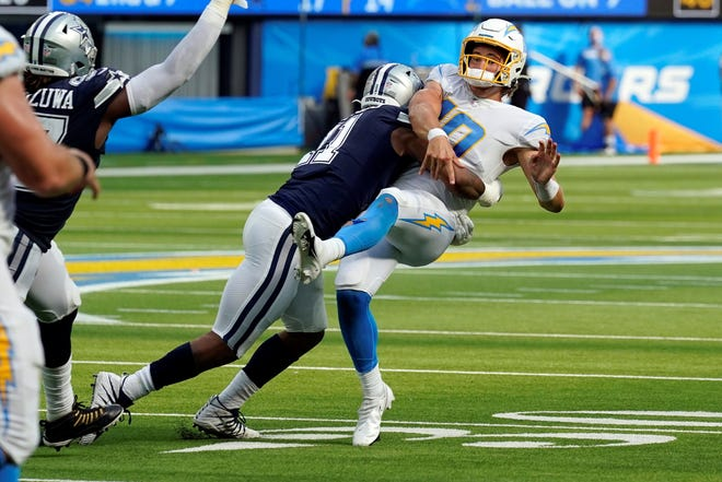 Los Angeles Chargers quarterback Justin Herbert is hit by Dallas Cowboys linebacker Micah Parsons as he throws during the second half of an NFL football game Sunday, Sept. 19, 2021, in Inglewood, Calif. (AP Photo/Gregory Bull)