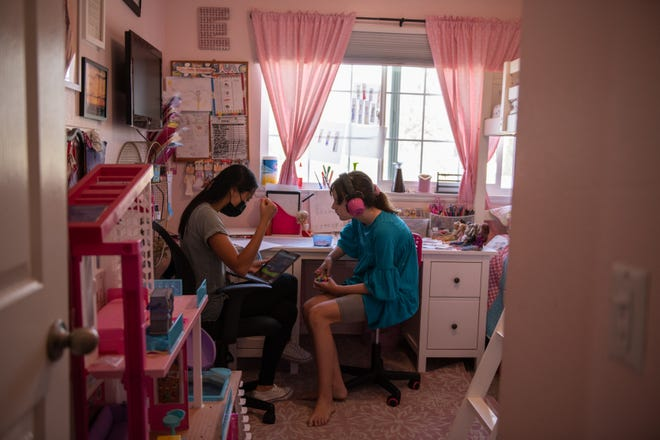 """Ellie Fitzgibbons sits in her room with a behavioral therapist during class time in Monrovia, on Wednesday, Sept. 15, 2021. """"There is no way to go back with 37 kids in a classroom,"""" Julie Fitzgibbons, the mother of triplets, said. """"With masks and not being able to communicate very well, and autism, there is just no way we can go back like normal."""""""