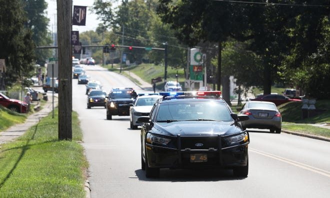 A long line of first responder vehicles escort the body of John Fortner, a Licking County Sheriff's Office Dispatcher who died after a car wreck on Friday, to Bolin-Dierkes Funeral Home in Zanesville on Sunday.