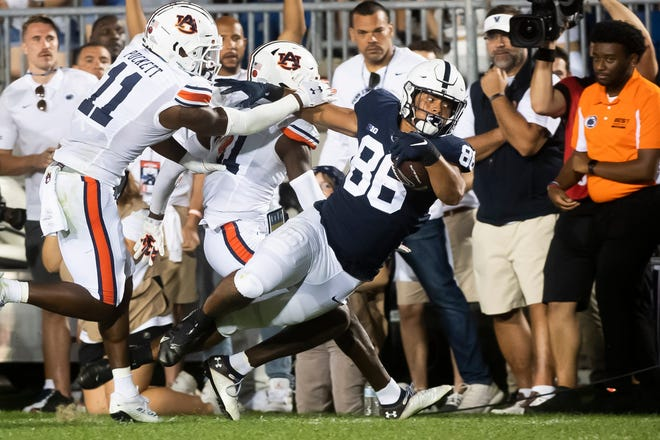 Penn State's Brenton Strange (86) is pushed out of bounds by a pair of Auburn defenders after making a catch in the fourth quarter at Beaver Stadium.