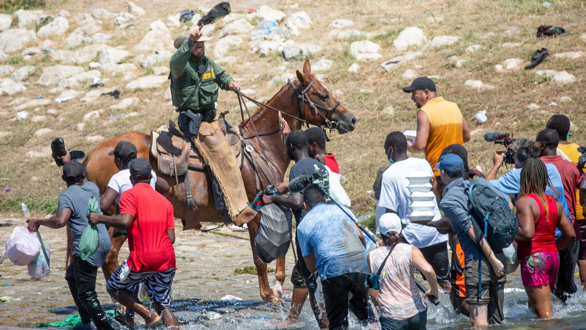 U.S. Border Patrol agents deter Haitians from returning to the U.S. on the bank of the Rio Grande after migrants crossed back to Mexico for food and water on Sept. 19, 2021.