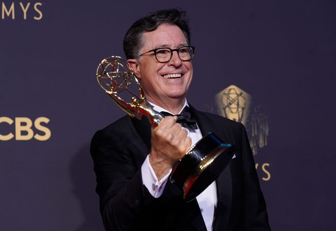 """Stephen T. Colbert poses with the award for outstanding variety special (live) for """"Stephen Colbert's Election Night 2020: Democracy's Last Stand Building Back America Great Again Better 2020"""" at the 73rd Primetime Emmy Awards on Sunday."""