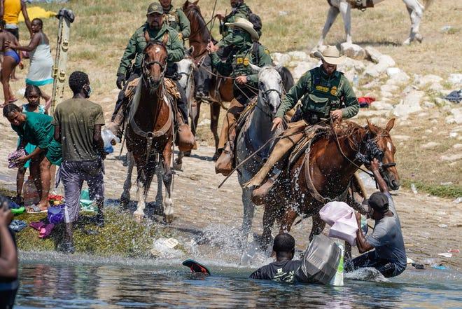Des agents des douanes et des patrouilles frontalières américaines à cheval tentent d'empêcher des migrants haïtiens d'entrer dans un campement sur les rives du Rio Grande, près du pont international Acuna Del Rio à Del Rio, Texas, le 19 septembre 2021.