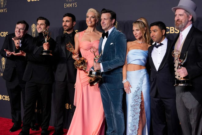 """""""Ted Lasso"""" cast members Jeremy Swift (far left), Phil Dunster, Brett Goldstein, Hannah Waddingham, Jason Sudeikis, Juno Temple, Nick Mohammed and Brendan Hunt celebrate their win for best comedy series at the 73rd Emmy Awards."""