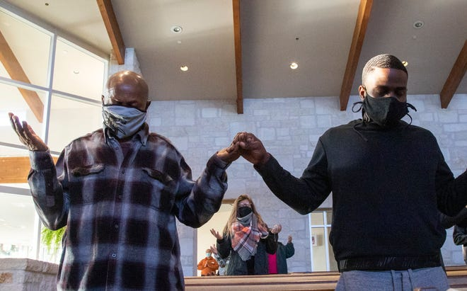 Vincent Edwards, 68, left, holds hands with his son Kingsly Edwards, 32, during a Sunday service at St. Albert the Great Catholic Church in December. Prayer can bring communities together.