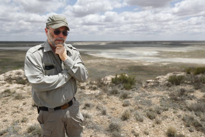 Biologist Jude Smith stands on a bluff overlooking an empty saline lake at the Muleshoe National Wildlife Refuge outside Muleshoe on May 18. The lake is fed by the Ogallala Aquifer, which has been become increasingly dry because of irrigation and drought. [AP PHOTO/MARK ROGERS]