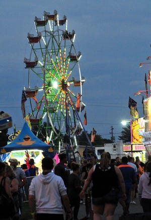 The Ferris wheel lights up as fairgoers take in games and rides at the Ashland County Fair Monday, Sept. 20, 2021.   LIZ A. HOSFELD/FOR TIMES-GAZETTE.COM