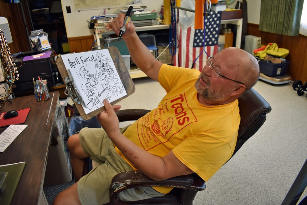 Cartoonist Rick Lem shows a cartoon from his archive at his home office near Kelley on July 15, 2021.