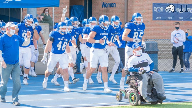 The Hillsdale Charger football team led onto the field by Jack Wolf.