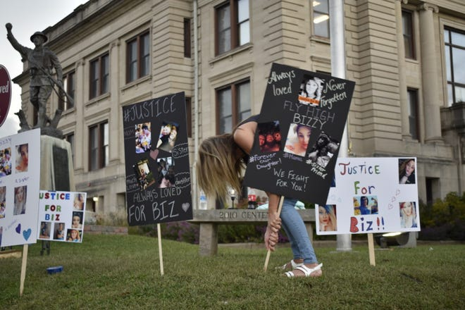 """Vickie  Edwards helps display signs in Spencer Monday at an Owen County Courthouse vigil for Elizabeth """"Biz"""" Stevens, who was killed in Owen County last week."""
