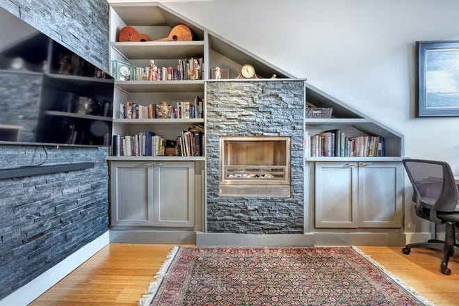 """In the living room, built-in bookcases fitted into the angled walls that also provide decorative spaces are more than practical as they draw even more attention to the unique angular lines like the """"matching"""" stone wall at right angles to the fireplace."""
