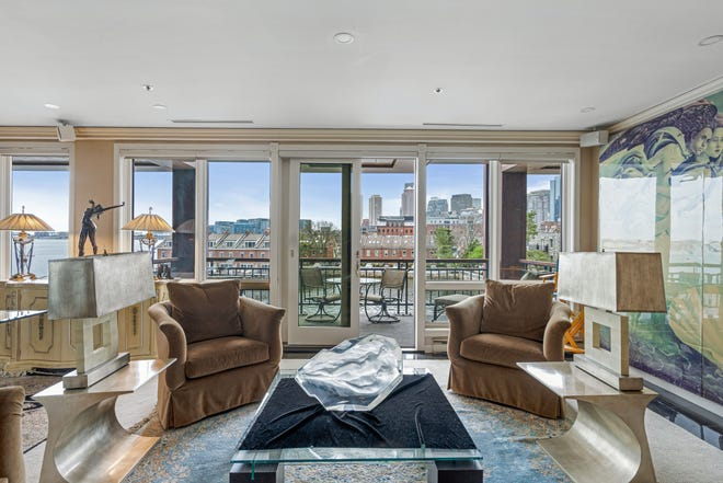 The family room offers great views, a hidden wood-burning fireplace and a large Greek God glass mural along with access to a deck.