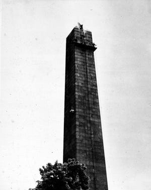 In 1958, workers were busy steam-cleaning the Bunker Hill Monument. The ladder on the apex was pushed up by a man who stood at the top of the ladder on the swinging stage with support from a second man standing on the ladder below him. Learn more from Digital Commonwealth at www.digitalcommonwealth.org.