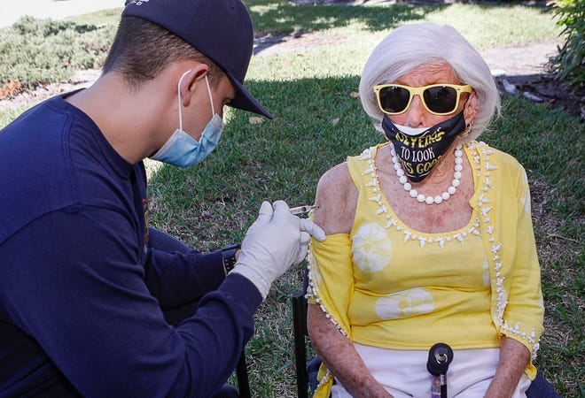 """Palm Beach resident Jane Smith, 102, is administered the COVID-19 Moderna vaccine at Fire Rescue Station #3, Tuesday, January 5, 2021. """"I didn't feel a thing,"""" Smith said. DAMON HIGGINS/PALM BEACH DAILY NEWS"""