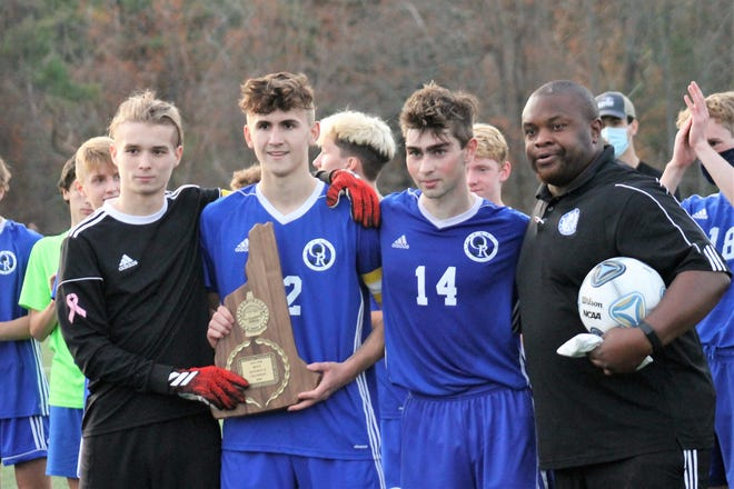 The Oyster River boys celebrated the program's 13th state soccer championship in 2020, a 1-0 win over Bow in double overtime. Pictured, from left, are captains John Kell, Caden Leader and Aidan Kelley, and coach Akan Ekanem.