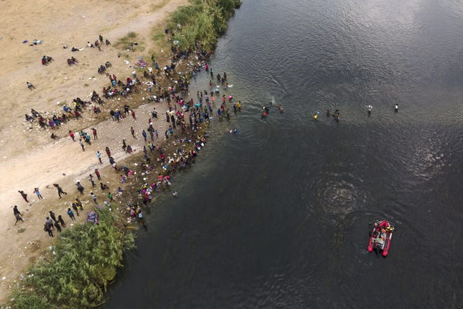A Mexican rescue boat chugs along the Rio Grande, bottom right, as migrants, many from Haiti, wade across the river into Del Rio, Texas, Tuesday, Sept. 21, 2021. The options remaining for thousands of Haitian migrants straddling the Mexico-Texas border are narrowing as the United States government ramps up to an expected six expulsion flights to Haiti and Mexico began busing some away from the border. (AP Photo/Julio Cortez)