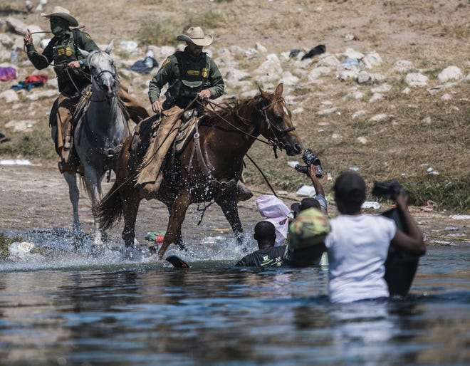 U.S. Customs and Border Protection mounted officers attempt to contain migrants as they cross the Rio Grande from Ciudad Acuña, Mexico, into Del Rio, Texas. Thousands of Haitian migrants have been arriving to Del Rio, Texas, as authorities attempt to close the border to stop the flow of migrants. (AP Photo/Felix Marquez)
