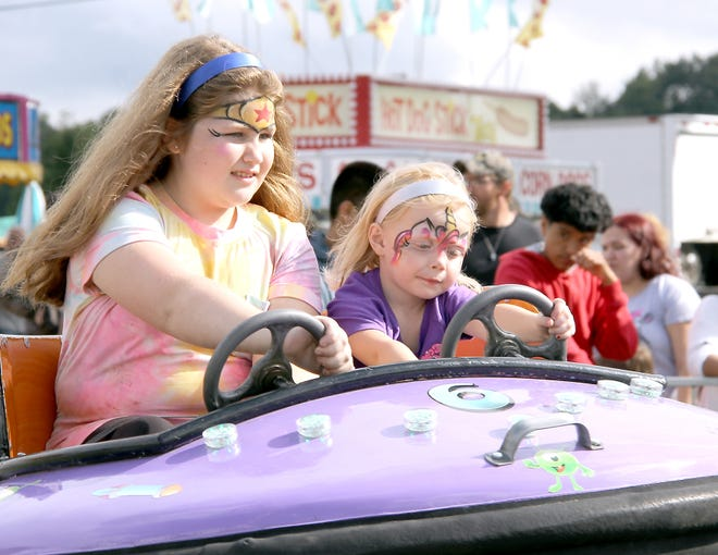 """Alexis Woods, 9, of White Pigeon, and her friend Natalie Lovely, 3, embraceda full range of """"Kids Day"""" attractions Monday at the St. Joseph Grange Fair."""
