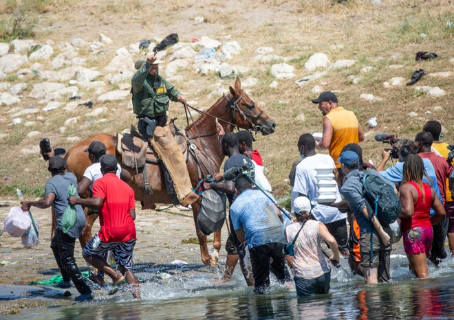 U.S. Border Patrol agents deter Haitians from returning to the U.S. on the bank of the Rio Grande after migrants crossed back to Mexico for food and water on Sept. 19.