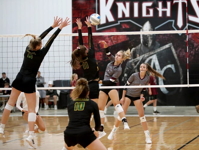 Aberdeen Roncalli middle hitters Madelyn Bragg and Ava Hanson attempt to block Aberdeen Christian outside hitter Mary Fites' hit during the first set of Monday's game at Aberdeen Christian. American News photo by Jenna Ortiz, taken 09/20/2021.