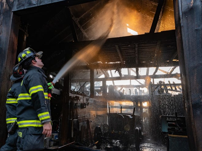 Firefighters spray water on a barn fire at 218 Davis Road in Westminster on Monday.