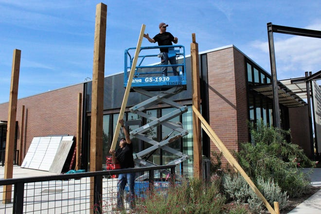 Employees with Padierna Contracting, a millwork installation company, work on the exterior of The Biscuit Bar, which could be the next business to open at Allen Ridge.