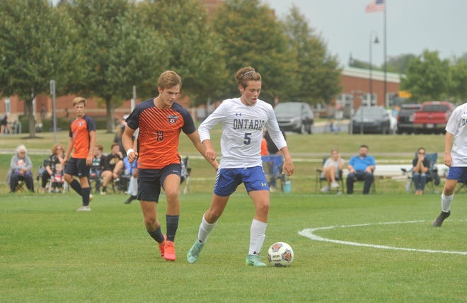 Ontario's Jack Hart drives through the middle of the pitch as Galion's Sam Albert closes in.