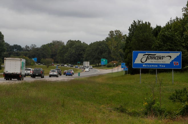 Cars heading east on Interstate 24 drive past the Tennessee welcome sign at the Tennessee-Kentucky border in Oak Grove, KY., on Monday, Sept. 20, 2021.