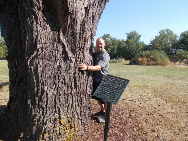 Frank Pierce, vice chairman of the Clyde Street Tree Commission, is the first to HUG-a-Tree, which is part of the city's Arbor Day ceremony Saturday.