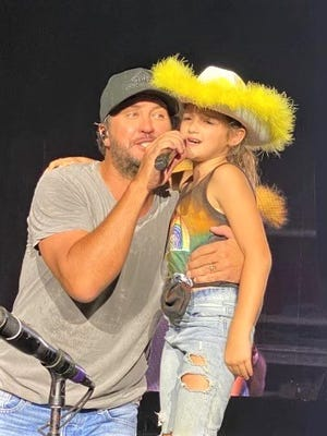 Lancaster resident Jemma Hill, 9, sings with country artist Luke Bryan Friday after he called her onstage during his concert on the Miller Family Farm near Baltimore.