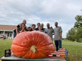 """Scott Bayuk and family set a Kentucky state record at the 2021 """"Great Pumpkin & Watermelon Weigh Off,"""" a Meade County tradition, with a pumpkin that weighed in at almost 2,000 pounds."""