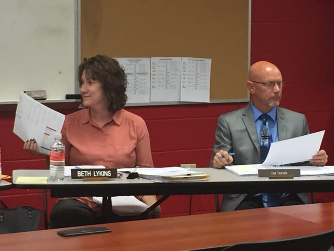 Shelby treasurer Barb Lykins makes a point at Monday's school board meeting while Superintendent Tim Tarvin reviews paperwork.