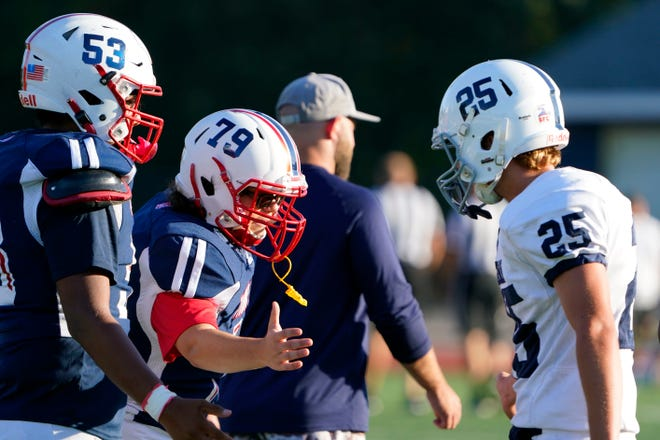Mendham lineman Shane Sullivan (79) high-fives a Chatham football player after a junior varsity game on Monday, Sept. 20, 2021, in Chatham.