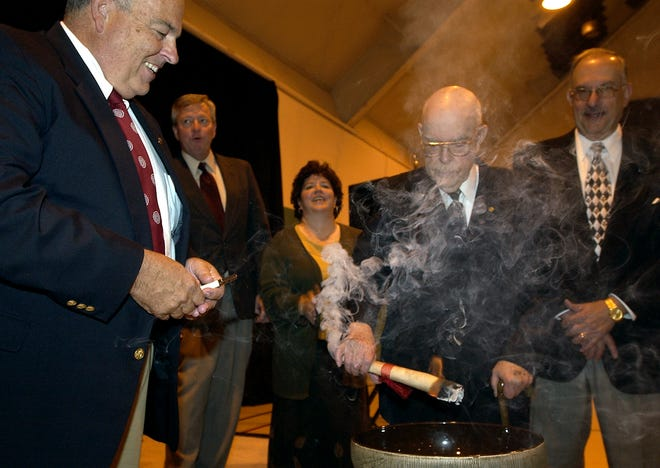 Wally Horton, former executive director of Port Authority, holds the 10-year mortgage worth approximately $11 million while it is set aflame during the 10-year anniversary celebration of Boeing in Heath in 2006.