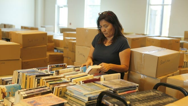 Sharon Blue Eyes of the Farmington Public Library staff sorts books before the annual book sale at the institution in August 2017. The event returns to the library this weekend.