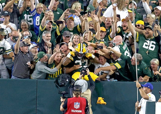 Green Bay Packers running back Aaron Jones (33) does the Lambeau Leap after scoring a touchdown during second quarter of the Green Bay Packers game against the Detroit Lions at Lambeau Field in Green Bay on Monday, Sept. 20, 2021.