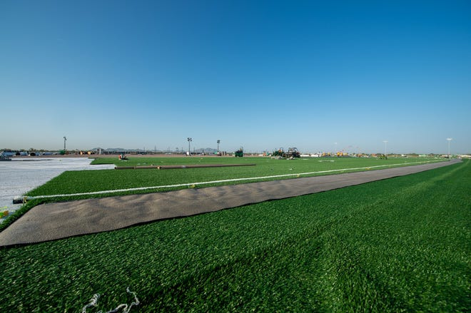 Workers install turf fields at Bell Bank Park in Mesa, Arizona.