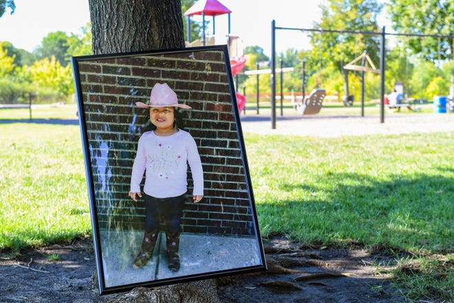 A poster of 4-year-old Nytalia Ashes rests against a tree at one of her favorite spots to play on Tuesday, September 21, 2021, at Dunham Park in Sioux Falls. Nytalia died after a tree branch fell on her family's tent during a storm at a Minnesota campground.