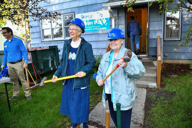 Sister Dorothy Manuel and Sister Karen Streveler pose for photographs with sledge hammers during a kick-off event at a new Habitat for Humanity project house Tuesday, Sept. 21, 2021, in St. Joseph. The house was donated to Habitat for Humanity by Sisters of the Order of St. Benedict.