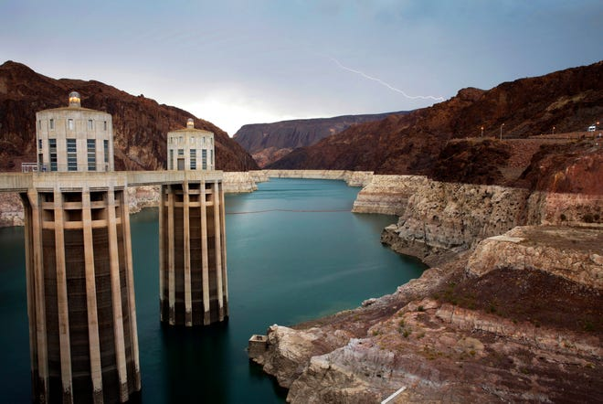 In this July 28, 2014, file photo, lightning strikes over Lake Mead near Hoover Dam that impounds Colorado River water at the Lake Mead National Recreation Area in Arizona. (AP Photo/John Locher, File)