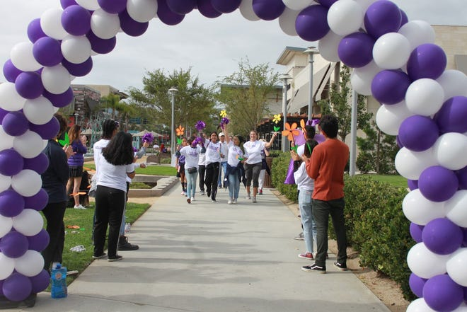 Participants in the 2019 West Ventura County Walk to End Alzheimer's make their way toward the finish line as bystanders applaud.