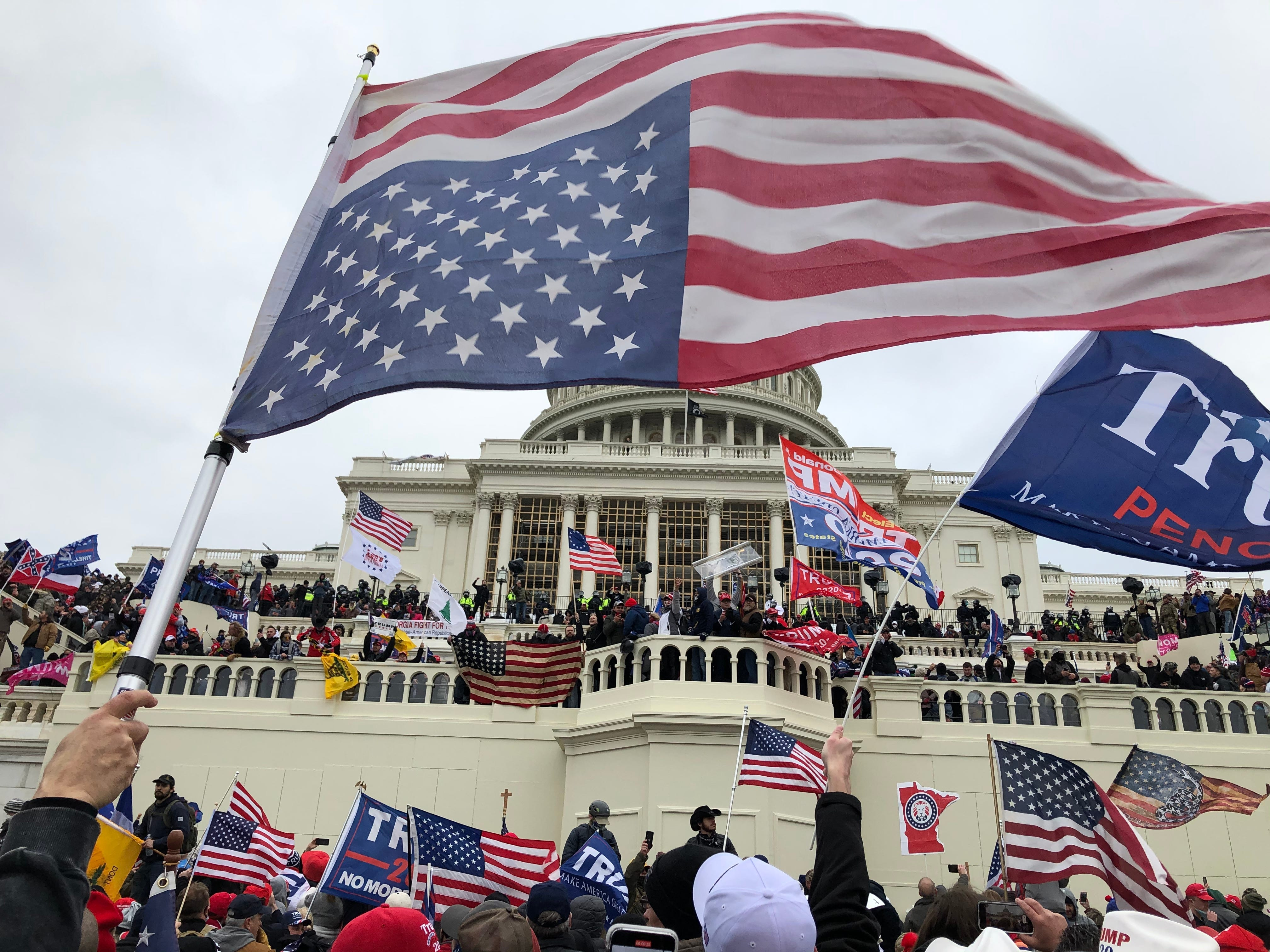 Rioters stand on the West front of the U.S. Capitol building to protest the official election of then-President-elect Joe Biden on Jan 6, 2020.