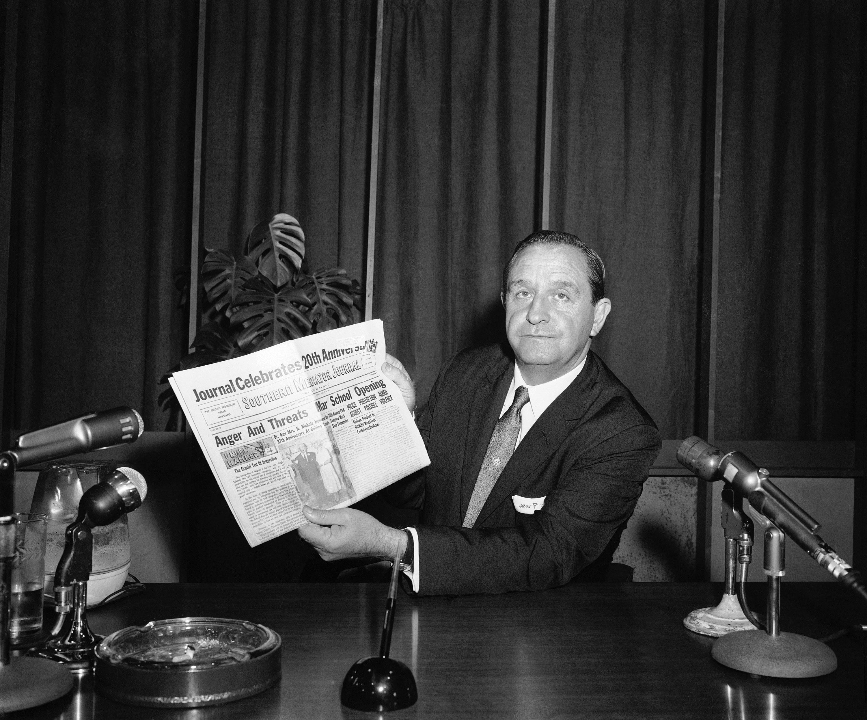 """Gov. Orval Faubus shows his television audience a local black newspaper headline: """"Anger and Threats Mar School Opening"""" in Little Rock, Sept. 3, 1957. He then directed the National Guard to maintain """"peace and order"""" at Central High School where racial integration was scheduled."""