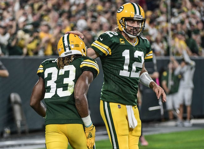 Green Bay Packers running back Aaron Jones celebrates with quarterback Aaron Rodgers after scoring a touchdown in the first quarter against the Detroit Lions at Lambeau Field.