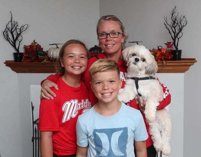 Season Erwin holds her dog, Chewy, as she stands with her children Athena, left, and Paxton in her home Sept. 20 in Green. Erwin was struck by a drunken driver while running in 2015. She has recovered from her severe injuries and will be running in a marathon this month in Columbus.