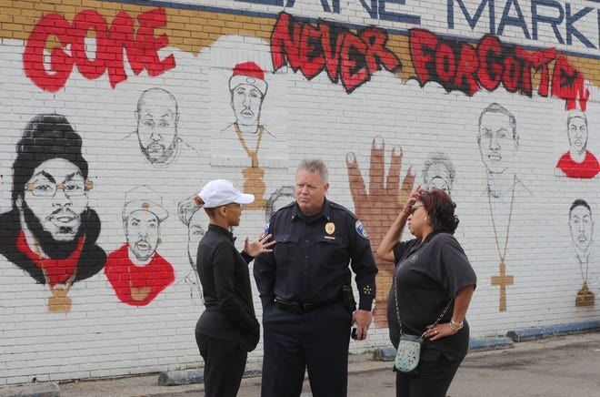 Akron Councilwoman Tara Samples, from left,  Police Chief Steve Mylett and Ward 5 Precinct Capt. Jennifer Gulley-Walker talk Wednesday in the parking lot of the Lovers Lane Market in Akron. Portraits of 14 slain people are on the wall behind them.