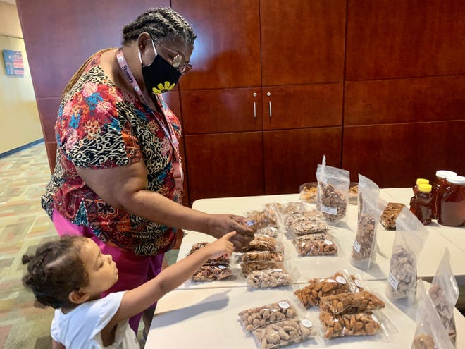 Dorothy Williams and her granddaughter Aubree Davey, 3, of Augusta check out pralines Tuesday at the Veggie Park Farmers Market.