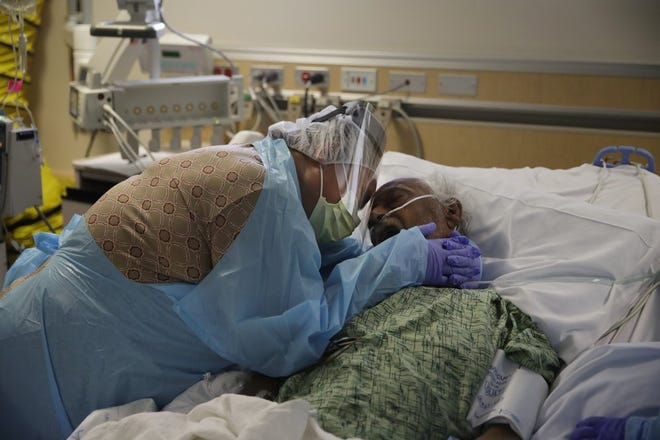 Among the unvaccinated, heartbreaking scenes such as this will continue. Romelia Navarro, 64, weeps while hugging her husband, Antonio, in his final moments in a COVID-19 unit at St. Jude Medical Center in Fullerton, Calif.