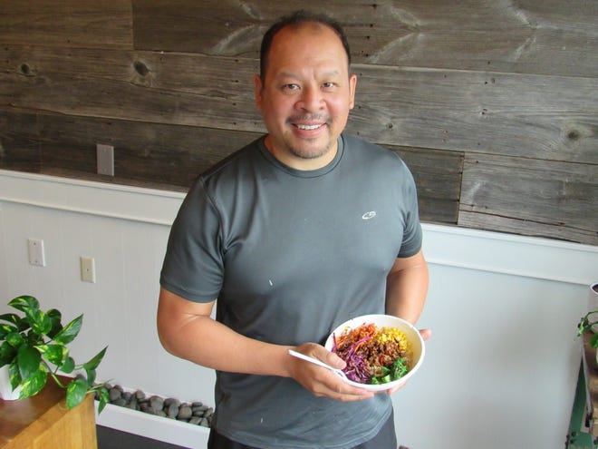 Rhome Ruanphae holds up a self-crafted Thai bowl at his new restaurant, Buddha Bowl, which he opened Sept. 15 in the old Blunch spot, 2973 N. High St. in Clintonville.