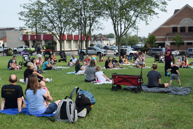 Southwest Public Libraries youth-services assistant Linda Bils (right) reads to more than 70 children and parents during the first outdoor storytime in Town Center Park in Grove City on Sept. 13.
